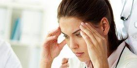 Stress bei der Arbeit: Frau mit Kopfschmerzen, Arztkittel, Hände an den Schläfen